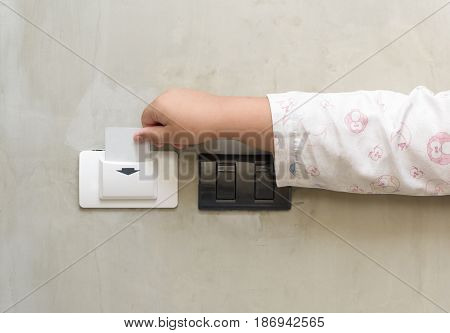 child putting key card switch in hotel room