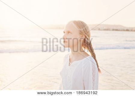 Happy Young Girl Walking at the Beach under the Morning Sun