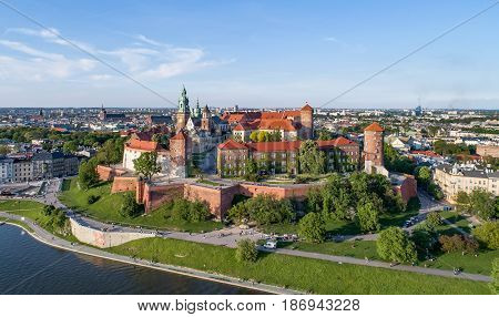 Krakow, Poland. Wawel hill with historic royal castle and cathedral, Vistula River, park and walking people. Aerial view at sunset. poster