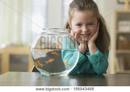 Caucasian girl standing next to fish bowl