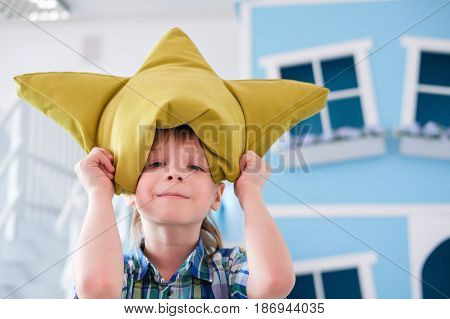 Portrait of a cute little school boy with yellow pillow crown.