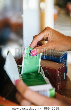 Unrecognizable woman taking a teabag from a box. Vertical indoors shot.