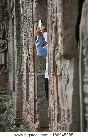 Tourist photographing Ta Prohm temple