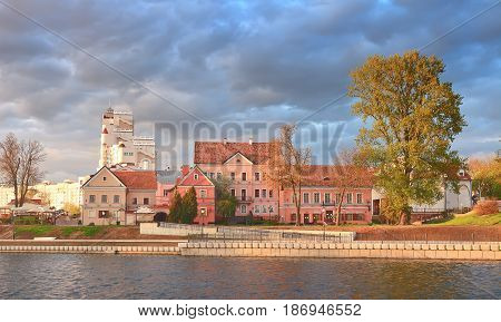 Landscape architecture of the European city on the river on a sunny day with gray textured clouds in the sky. Houses, trees on the river bank in the city center, carefree life, bright colors of architecture.
