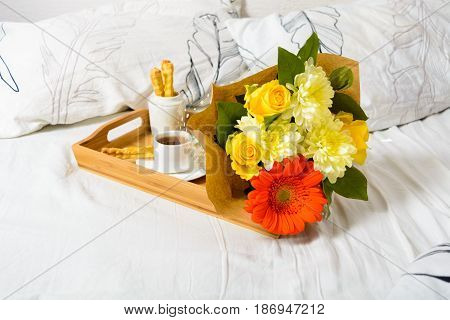 Tray With Coffee, Snack And Bouquet Of Flowers On Bed