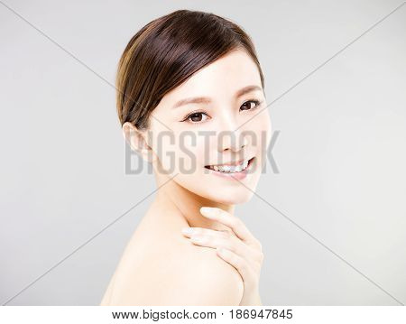 young smiling woman face with gray background