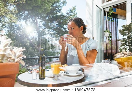 Horizontal outdoors shot of adult woman drinking hot beverage having breakfast in cafe.