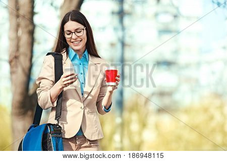 Young businesswoman walking using cellphone and having hot drink.