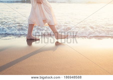 White Skirt Woman Legs Walking on Beach Vacation. Closeup of Barefoot Female Young Adult Lower Body Relaxing in Ocean Water on Summer Holiday Travel
