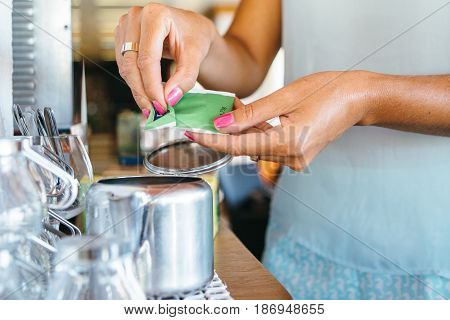 Horizontal indoors shot of hands of woman opening a teabag.