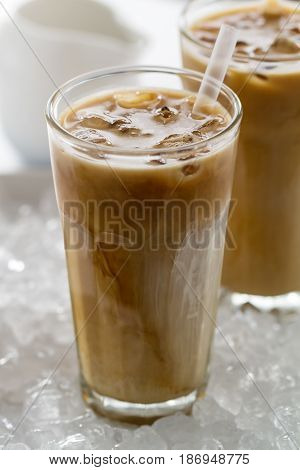 Tasty cold refreshing drink with coffee milk and ice in glass on ice background. Closeup.