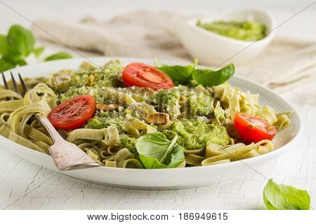Tasty appetizing italian pasta with sauce pesto tomatoes and pistachios on white plate. Horizontal.