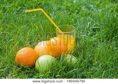 Fresh juice in glass staying on green grass near orange apples