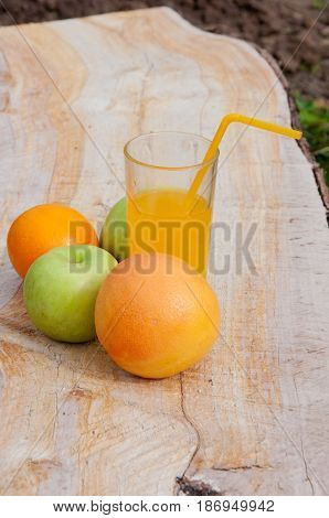 Fruits and fresh orange juice on wooden background
