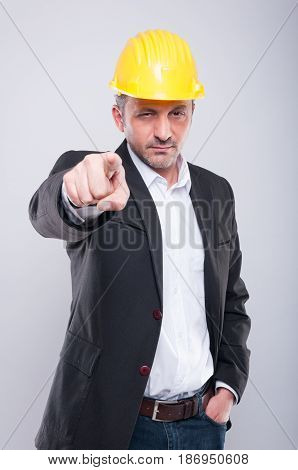 Portrait Of Foreman Wearing Hardhat Pointing Camera