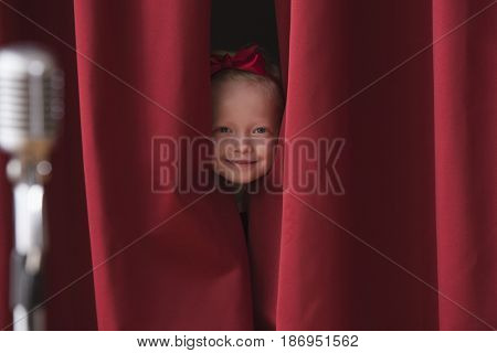 Caucasian girl peering from backstage