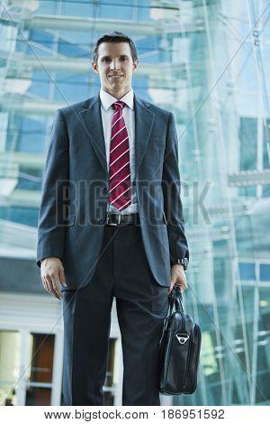 Caucasian businessman holding briefcase outdoors