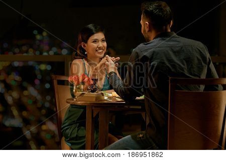 Young Filipino couple in love having date in restaurant at night