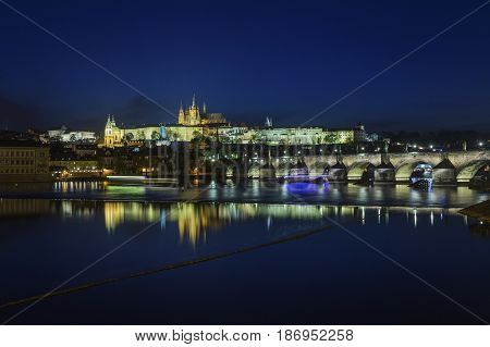 Prague Castle and Charles Bridge at night blue sky and river Czech republic