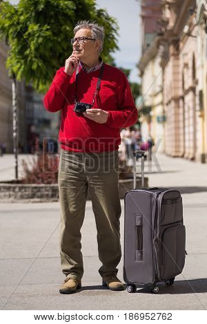 Senior man tourist has come to the city on a vacation but he doesn't know which way to go.