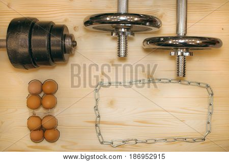 Dumbells on wooden floor. Gym flat lay background.