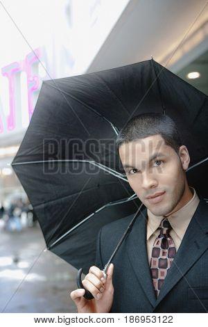 Hispanic businessman holding umbrella