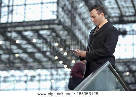 Hispanic businessman text messaging on cell phone in lobby
