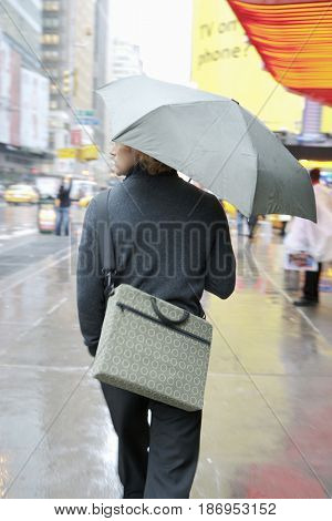 Caucasian businessman walking in rain with umbrella