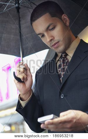 Hispanic businessman holding umbrella and text messaging on cell phone