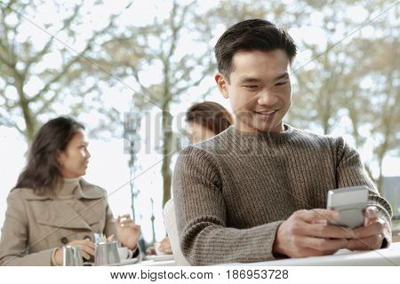 Asian man text messaging on cell phone in cafe