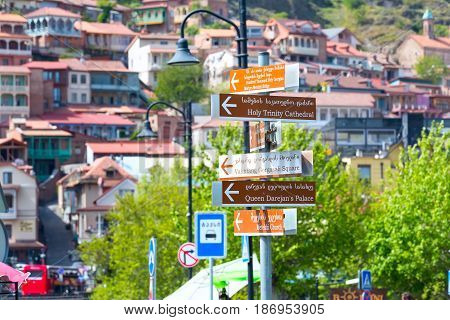 Tbilisi, Georgia - April 29, 2017: Signpost with landmarks of Tbilisi and background view of traditional georgian houses in Old Town
