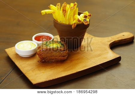 Well-done grilled marinated beef flank steak with ketchup, mustard and french fries on wooden board.