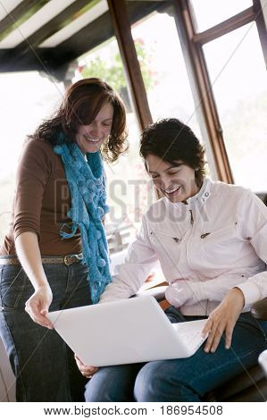 Hispanic women using laptop together