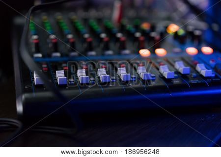 DJ mixer in a nightclub, mixing music. Tangled electric wires.