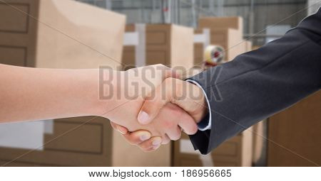 Digital composite of Cropped image of business people doing handshake in warehouse