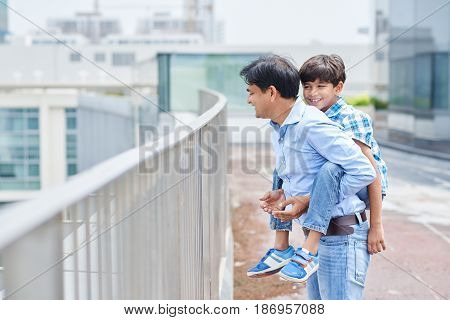 Cheerful Indian man giving piggyback ride to his son