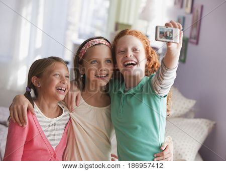 Girls taking self-portrait with digital camera
