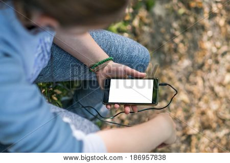 Cropped picture of female runner in warm clothes in autumn park using her phone