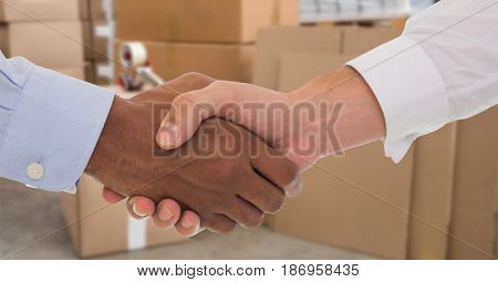 Digital composite of Business people shaking hands in warehouse