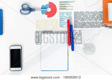 Top View Of Smartphone With Blank Screen, Empty Notebook With Markers, Scissors And Business Charts