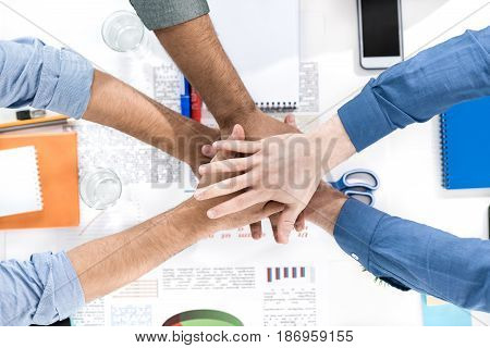 Close-up partial view of businessmen stacking hands while working on project together business teamwork concept