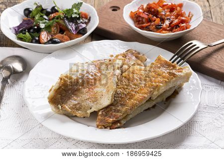 Fried rose fish fillet on a white plate. Sebastes norvegicus or ocean perch.