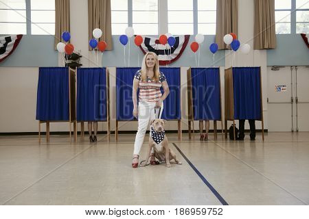 Woman and dog standing in polling place