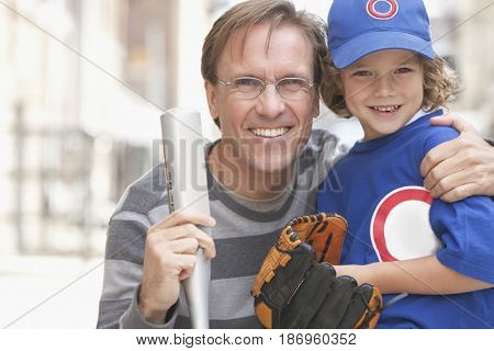 Caucasian boy playing baseball with father