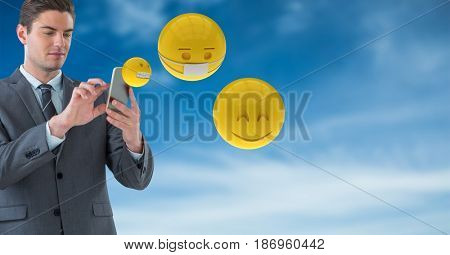 Digital composite of Businessman using smart phones while emojis flying against sky
