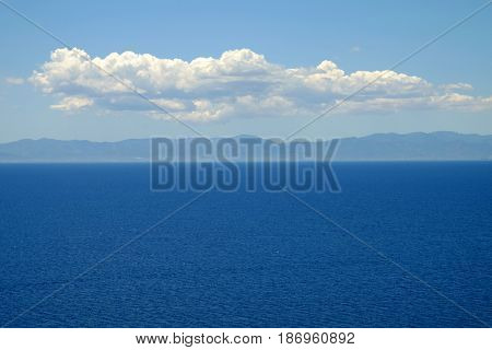 View on blue sea mountains sky and white clouds in Sardinia Italy.