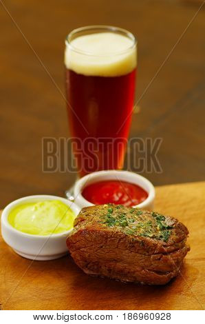 Close up of a well-done grilled marinated beef flank steak with ketchup, mustard with a glass of beer on wooden board.