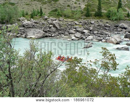 River rafting. Group of tourist floated on a boat. Altai Mountains, Russia.