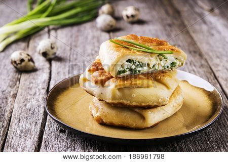 Patties with green onion, cottage cheese and egg filling on rustic wooden table. Fresh home baking. Selective focus