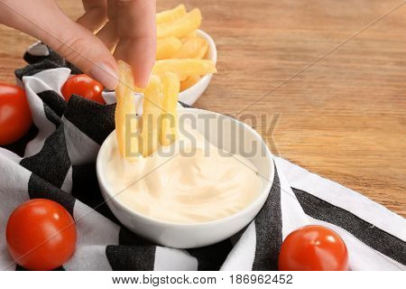 Hand of woman eating French fries with tasty mayonnaise sauce, closeup